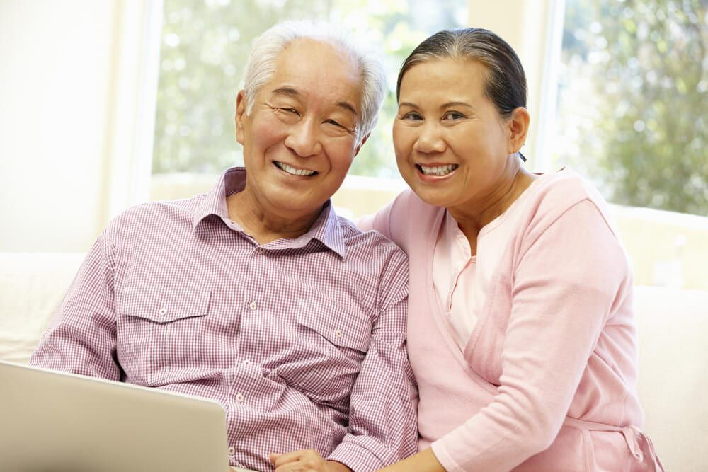 old couple with laptop smiling