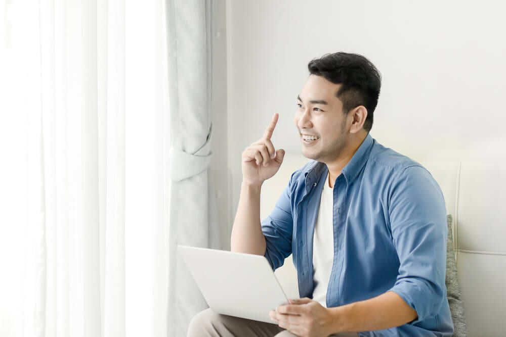 man getting an idea after researching on laptop